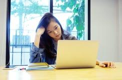 Ung asiatisk kvinna med frustrerat uttryck, medan arbeta med b?rbar datordatoren som hemifr?n arbetar, tillf?llig kontorslivsstil fotografering för bildbyråer