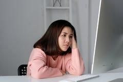 Ung asiatisk kvinna med frustrerat uttryck, medan arbeta på ca arkivbild