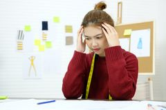 Ung asiatisk kvinna med frustrerat uttryck, medan arbeta på skrivbordet för modedesignstudio, emotionellt folk och kontorslivssti royaltyfri foto