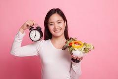 Ung asiatisk kvinna med klockan och sallad Royaltyfria Bilder