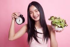 Ung asiatisk kvinna med klockan och sallad Royaltyfria Foton