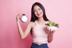 Ung asiatisk kvinna med klockan och sallad Arkivbilder