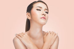 Ung asiatisk kvinna med korsade armar ren hud som vilar efter skincare, på rosa bakgrund Royaltyfri Foto