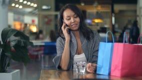 Ung asiatisk kvinna på telefonen, når att ha shoppat i galleria Arkivbild