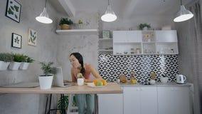 Ung asiatisk kvinna som äter det gröna äpplet och ser till skärmen av bärbara datorn lager videofilmer