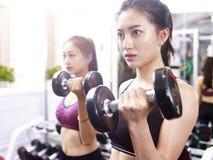 Ung asiatisk kvinna som övar att utarbeta i idrottshall royaltyfria bilder