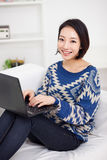 Ung asiatisk kvinna som använder bärbar dator Arkivfoto