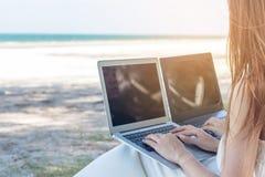 Ung asiatisk kvinna som använder bärbara datorn i klänningsammanträde på stranden, Gir royaltyfri foto