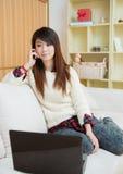 Ung asiatisk kvinna som använder en bärbar dator och en mobiltelefon Fotografering för Bildbyråer