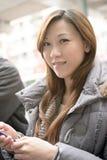 Ung asiatisk kvinna som använder mobiltelefonen royaltyfri bild