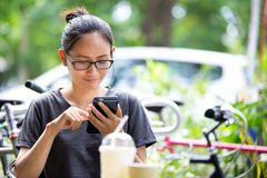 Ung asiatisk kvinna som använder smartphonen i trädgård Arkivbild