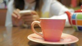 Ung asiatisk kvinna som använder smartphonen på restaurangen arkivfilmer