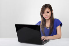 Ung asiatisk kvinna som arbetar med den isolerade bärbara datorn royaltyfri fotografi