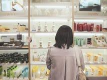 Ung asiatisk kvinna som in framme står av en hylla med skincareprodukter royaltyfri fotografi