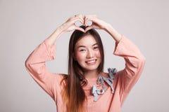 Ung asiatisk kvinna som gör en gest hjärtahandtecknet Royaltyfria Bilder