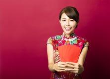ung asiatisk kvinna som ger röda påsar för rich Royaltyfri Foto