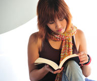 Ung asiatisk kvinna som läser en bok Arkivbilder