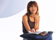 Ung asiatisk kvinna som läser en tidskrift royaltyfri fotografi