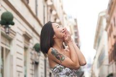 Ung asiatisk kvinna som ler genom att använda den stads- mobiltelefonvåren Royaltyfri Foto