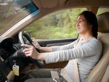 Ung asiatisk kvinna som ler, medan köra en bil Royaltyfri Fotografi
