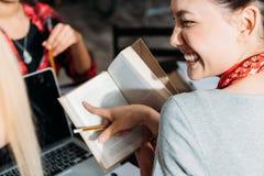 Ung asiatisk kvinna som ler och pekar med fingret på boken Arkivfoton