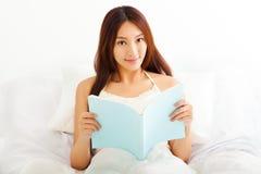Ung asiatisk kvinna som ligger i säng, medan läsa en bok Royaltyfri Fotografi
