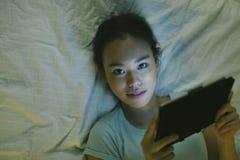 Ung asiatisk kvinna som ligger på säng och använder den digitala minnestavlan i natten Arkivbilder