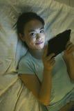 Ung asiatisk kvinna som ligger på säng och använder den digitala minnestavlan i natten Arkivfoton