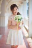 Ung asiatisk kvinna som luktar vita blommor Royaltyfria Bilder