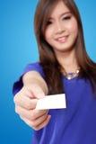 Ung asiatisk kvinna som räcker ett tomt vitt kort royaltyfri bild