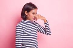 Ung asiatisk kvinna som rymmer hennes näsa på grund av en dålig lukt arkivfoton