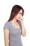 Ung asiatisk kvinna som rymmer hennes näsa på grund av en dålig lukt arkivbild