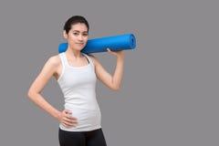 Ung asiatisk kvinna som rymmer hennes yoga matt på den sunda sportidrottshallen Yog Royaltyfria Foton