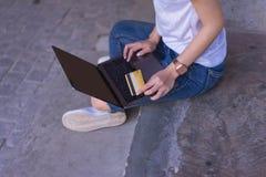 Ung asiatisk kvinna som sitter, medan genom att anv?nda en b?rbar dator och ett krediterings- eller debiteringkort p? det fria f? arkivfoto