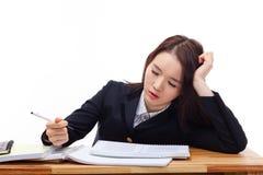 Ung asiatisk kvinna som sovar på skrivbordet. Fotografering för Bildbyråer