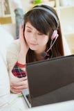 Ung asiatisk kvinna som tycker om musik med bärbara datorn Arkivfoto