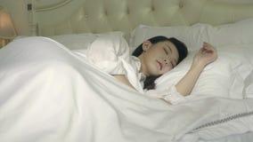 Ung asiatisk kvinna som vaknar upp i säng