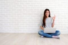 Ung asiatisk kvinna som visar det ok handtecknet och ler, medan arbeta med bärbar datordatoren i vitt rum med kopieringsspce, fol royaltyfria bilder