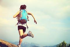Ung asiatisk kvinnafotvandrarespring på bergmaximum Arkivfoton