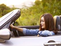 Ung asiatisk kvinnaridning i en konvertibel bil arkivfoton