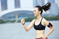 Ung asiatisk kvinnaspring förbi en sjö fotografering för bildbyråer