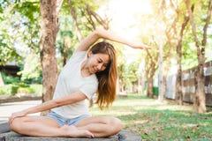 Ung asiatisk kvinnayoga håller stillhet och mediterar utomhus medan praktiserande yoga för att undersöka den inre freden royaltyfri bild