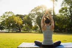 Ung asiatisk kvinnayoga håller stillhet och mediterar utomhus medan praktiserande yoga för att undersöka den inre freden arkivbilder