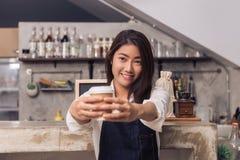 Ung asiatisk kvinnlig baristahåll per koppen kaffe som tjänar som till hennes kund med leende som omges med stångräknarebakgrund Royaltyfria Bilder