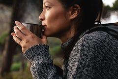Ung asiatisk kvinnlig fotvandrare som dricker kaffe Royaltyfri Foto
