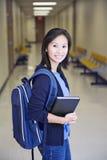 Ung asiatisk kvinnlig högskolaflicka i avläggande av examenkappan som isoleras på vit bakgrund arkivfoto