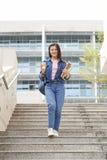 Ung asiatisk kvinnlig högskolaflicka i avläggande av examenkappan som isoleras på vit bakgrund royaltyfri bild