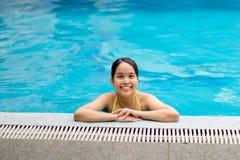 Ung asiatisk kvinnlig känsla som kopplas av i simbassäng Arkivbilder