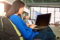 Ung asiatisk kvinnlig passagerare som använder bärbara datorn och den smarta telefonen, medan sitta på plats i slutlig korridor o arkivfoto