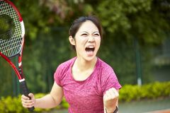 Ung asiatisk kvinnlig tennisspelare som firar, når att ha gjort poäng fotografering för bildbyråer